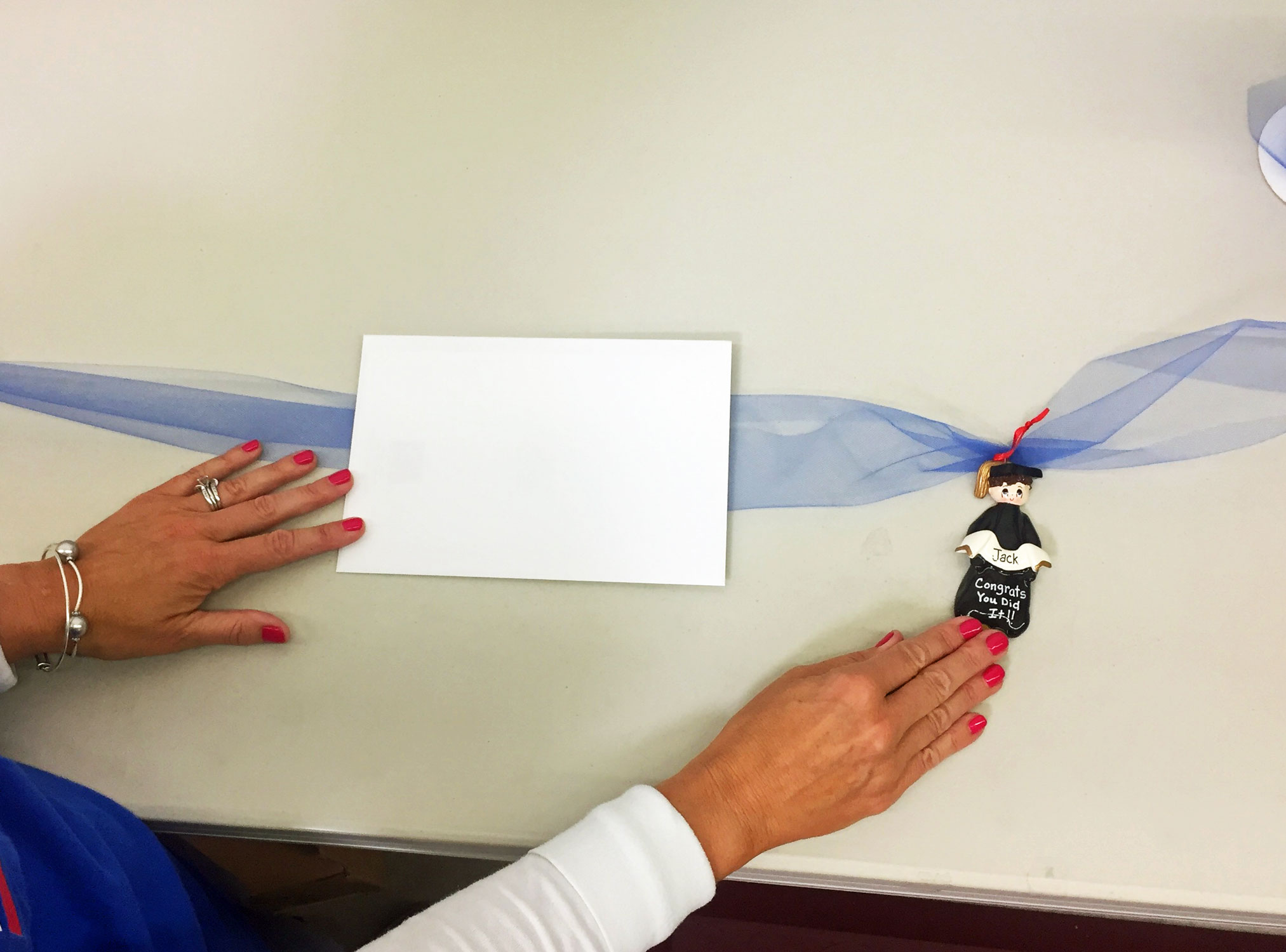 Step 3 is to lay the ribbon flat under the envelope with the ornament towards one end threaded | OrnamentShop.com