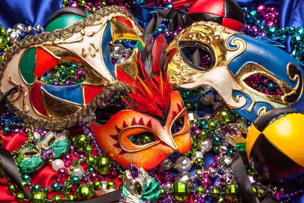 Colorful Mardi Gras masks on a background of colored beads and silk.