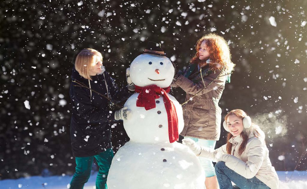 Beautiful young women enjoying building a snowman on a snowy winter day in forest