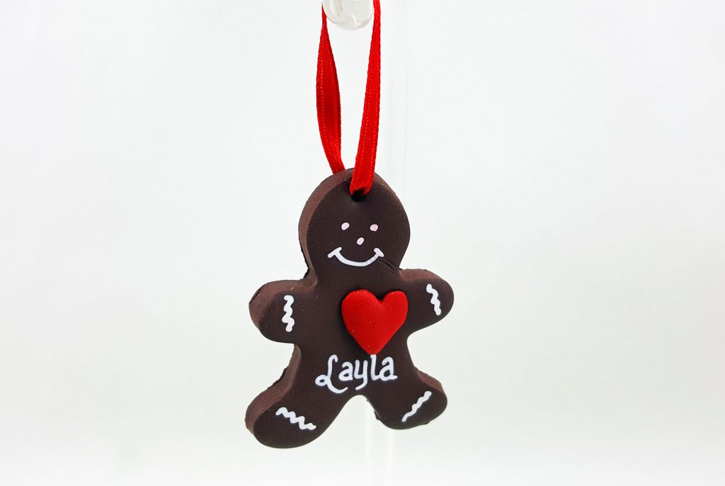 A DIY gingerbread man ornament with a red heart and white features, hung with a red ribbon | Ornamentshop.com
