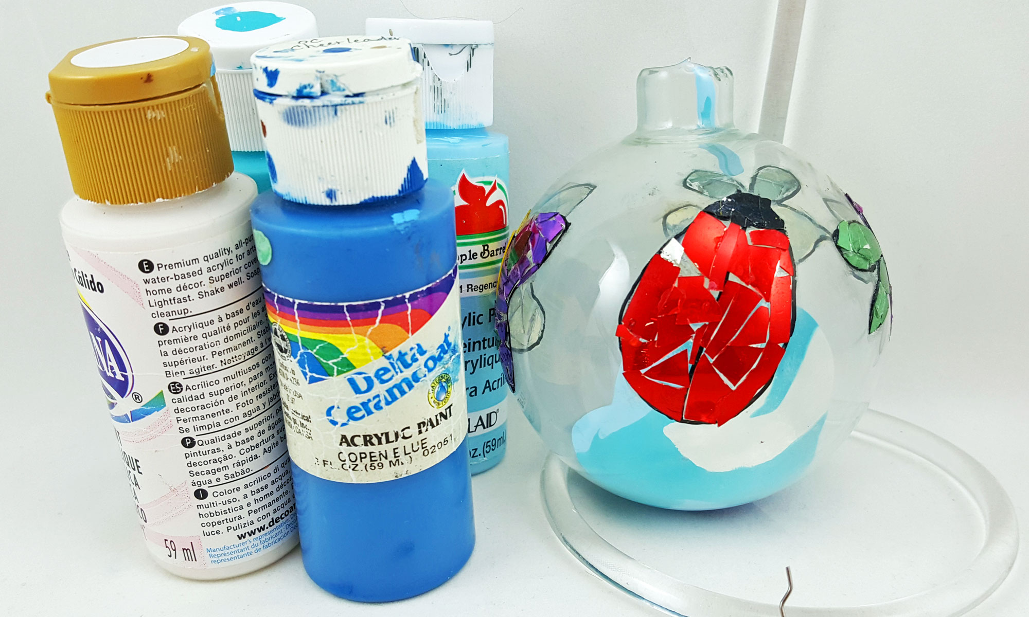 Step 3 is to pour blue and white paint into the clear glass ball and then swirl it around to coat the inside | OrnamentShop.com