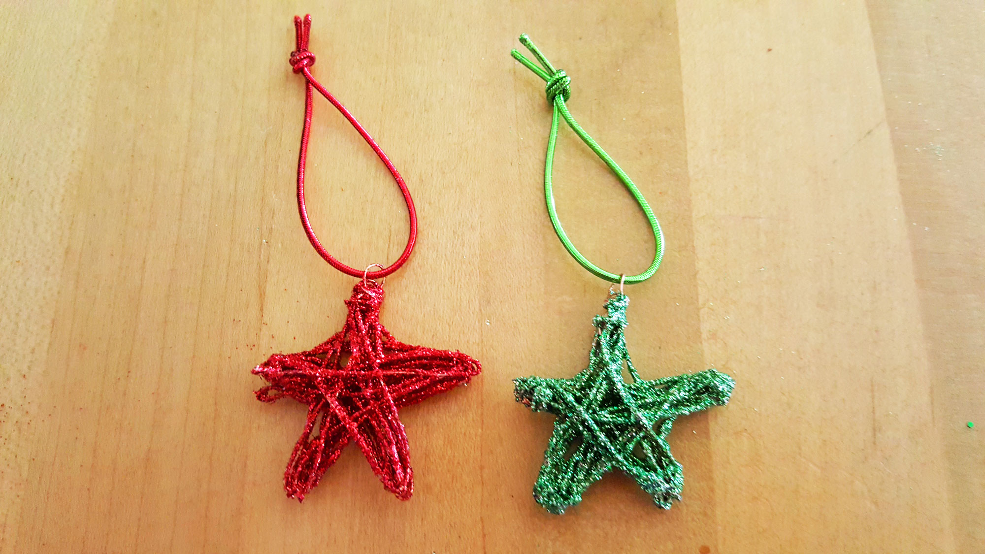 A red and green DIY star ornament side by side on a counter | OrnamentShop.com