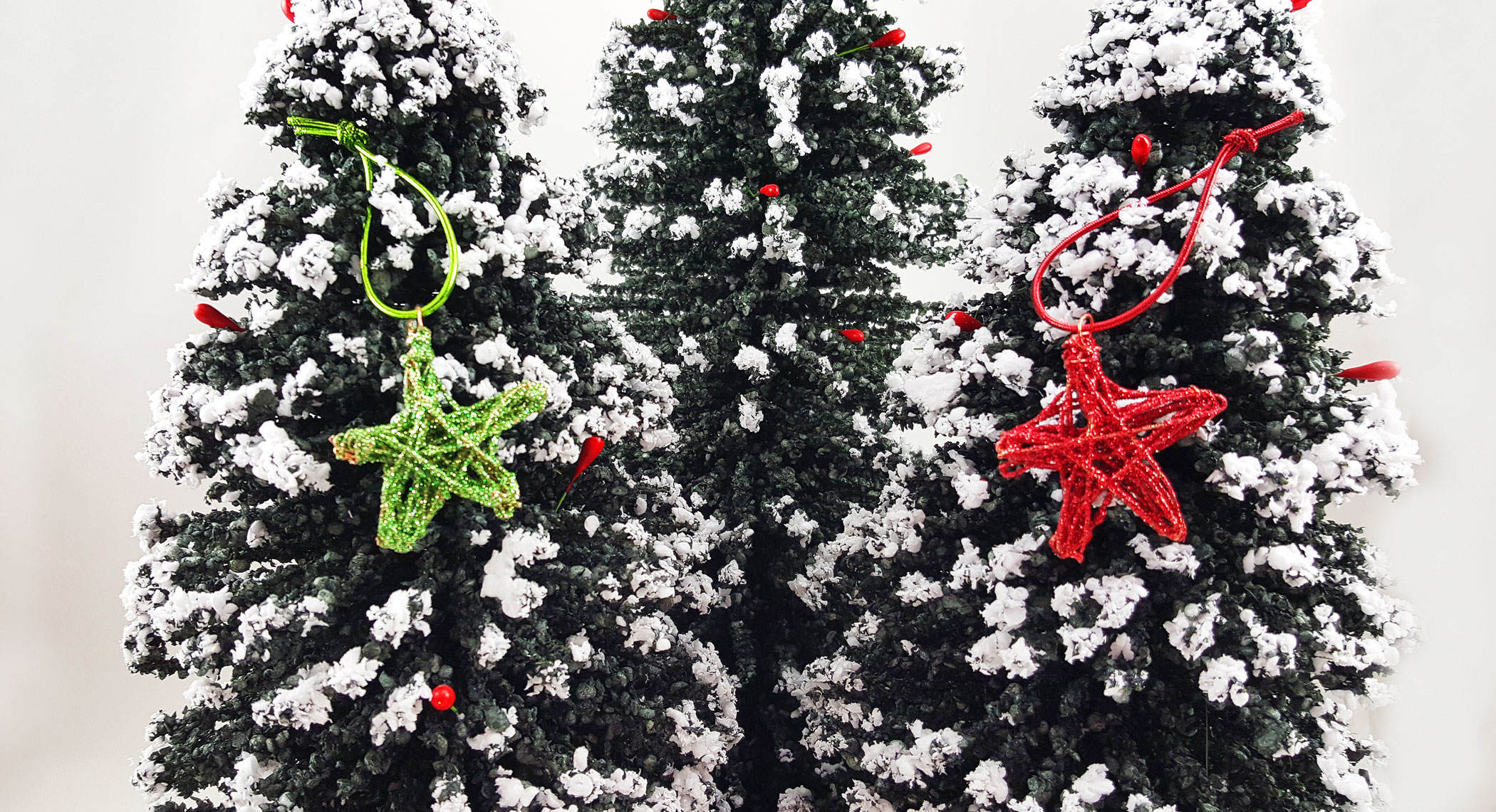 A red and green DIY star ornament hangs on miniature trees | OrnamentShop.com