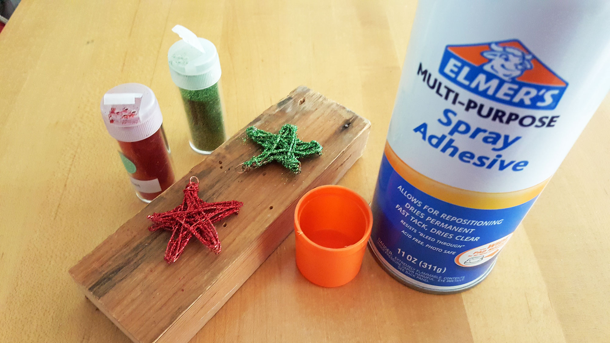 Step 5 is to use spray adhesive to coat the stars, then shake glitter all over them | OrnamentShop.com
