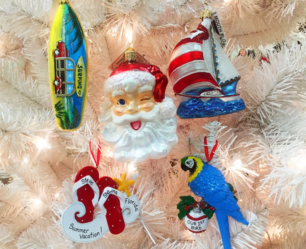An assortment of summer-themed ornaments, including a sailboat, parrot, flipflops, surfboard and a winking Santa | OrnamentShop.com