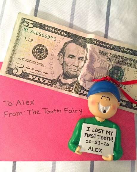 An ornament with a boy holding a sign and a gap in his smile that reads: I lost my first tooth! | OrnamentShop.com