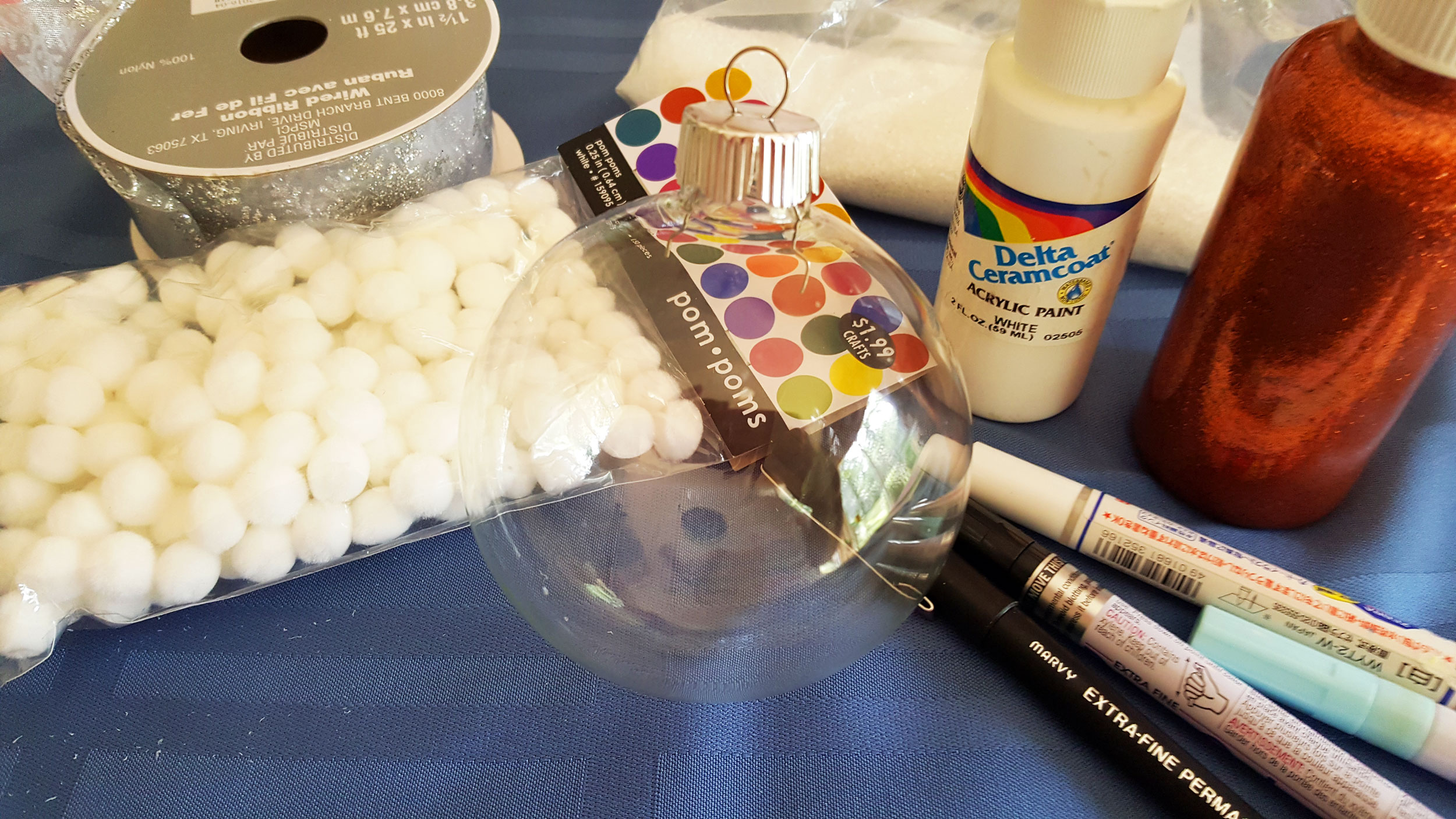 Fingerprint Snowman Ornament supplies including a glass ball, cotton balls, white paint and colorful paint markers. | OrnamentShop.com