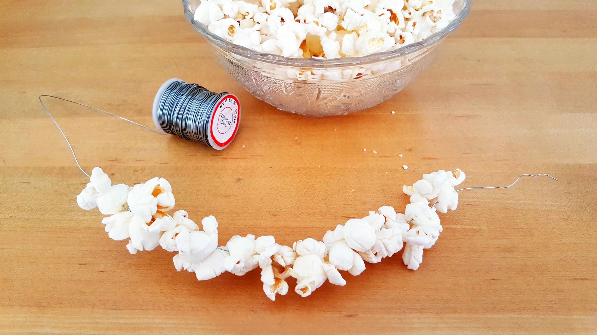 Step 1 is to string your popcorn along the wire. | OrnamentShop.com