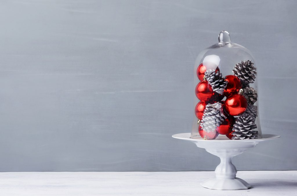 A glass cloche sits on a table filled with red baubles and pine cones for a Christmas theme. | OrnamentShop.com