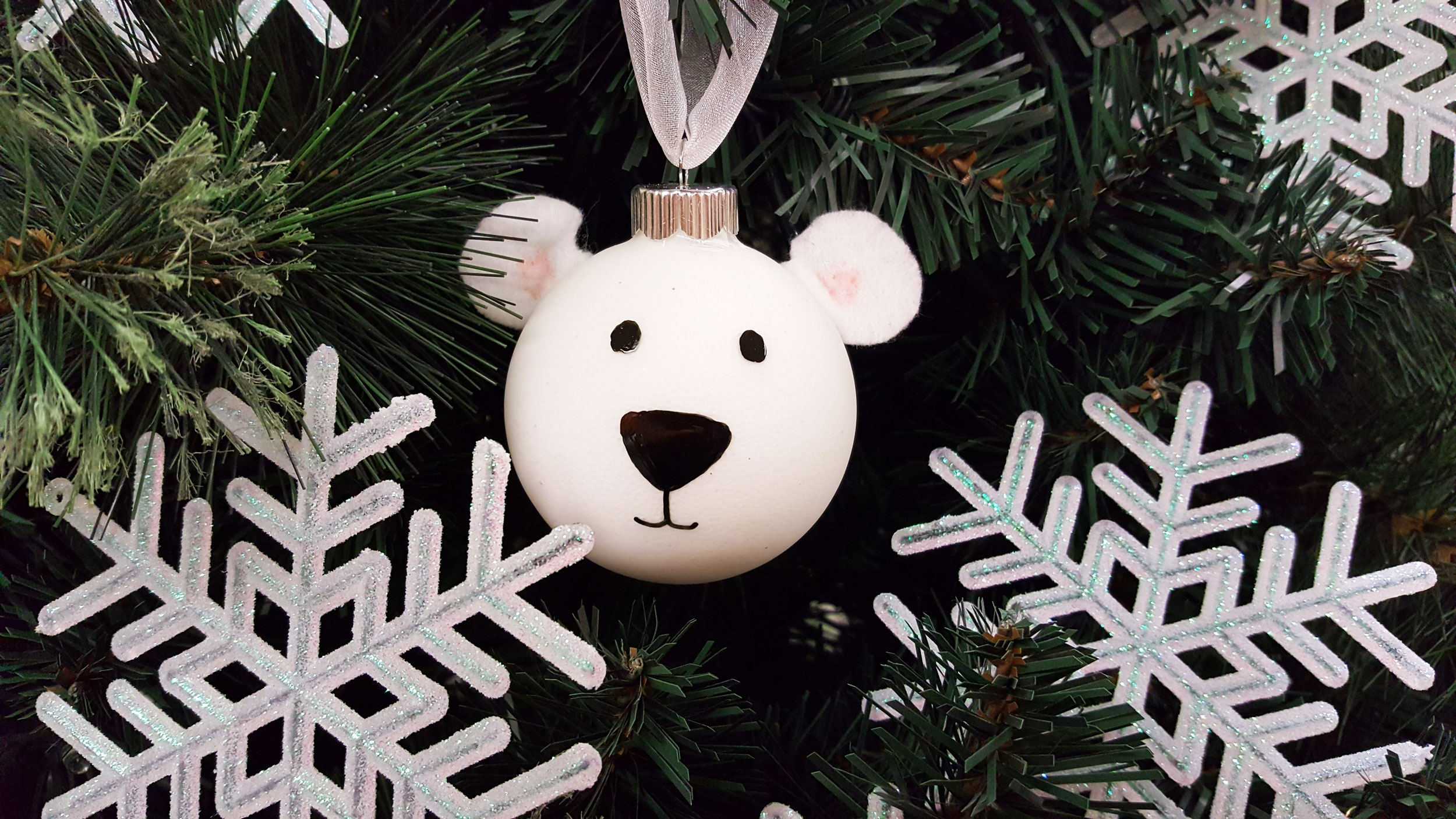 a white DIY polar bear ornament made from a bauble ornament and hiding in a tree behind giant snowflakes. | OrnamentShop.com