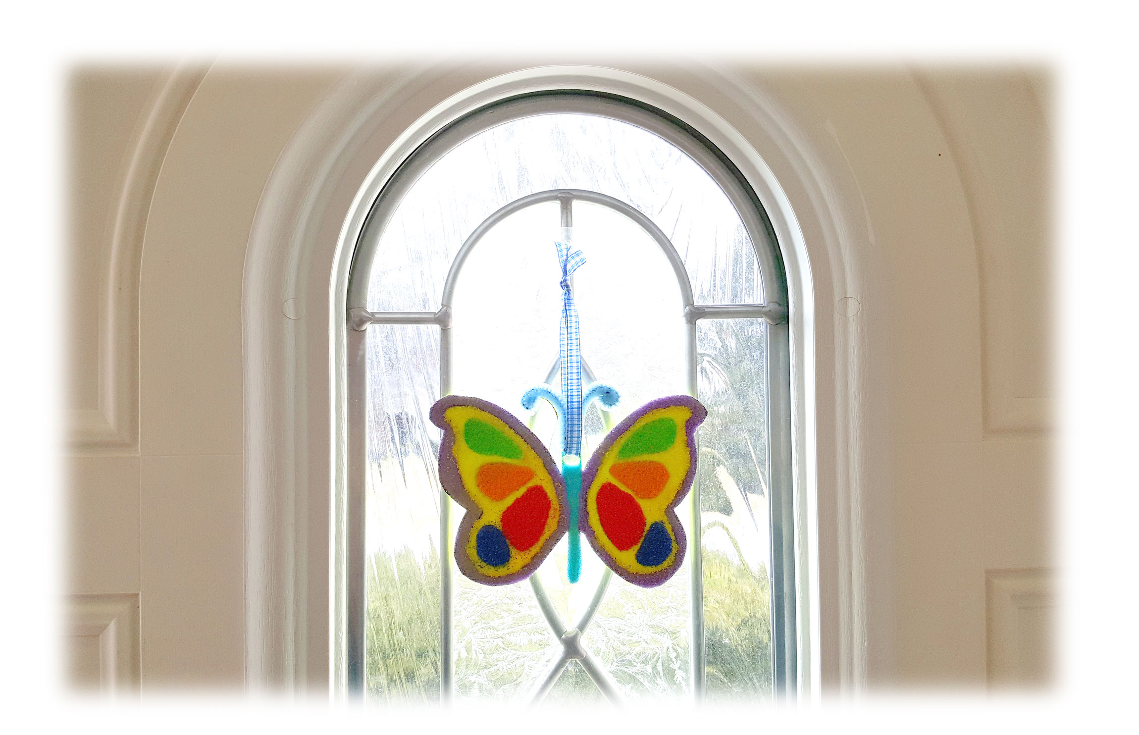 Sand Ornament hung in front of window. | OrnamentShop.com