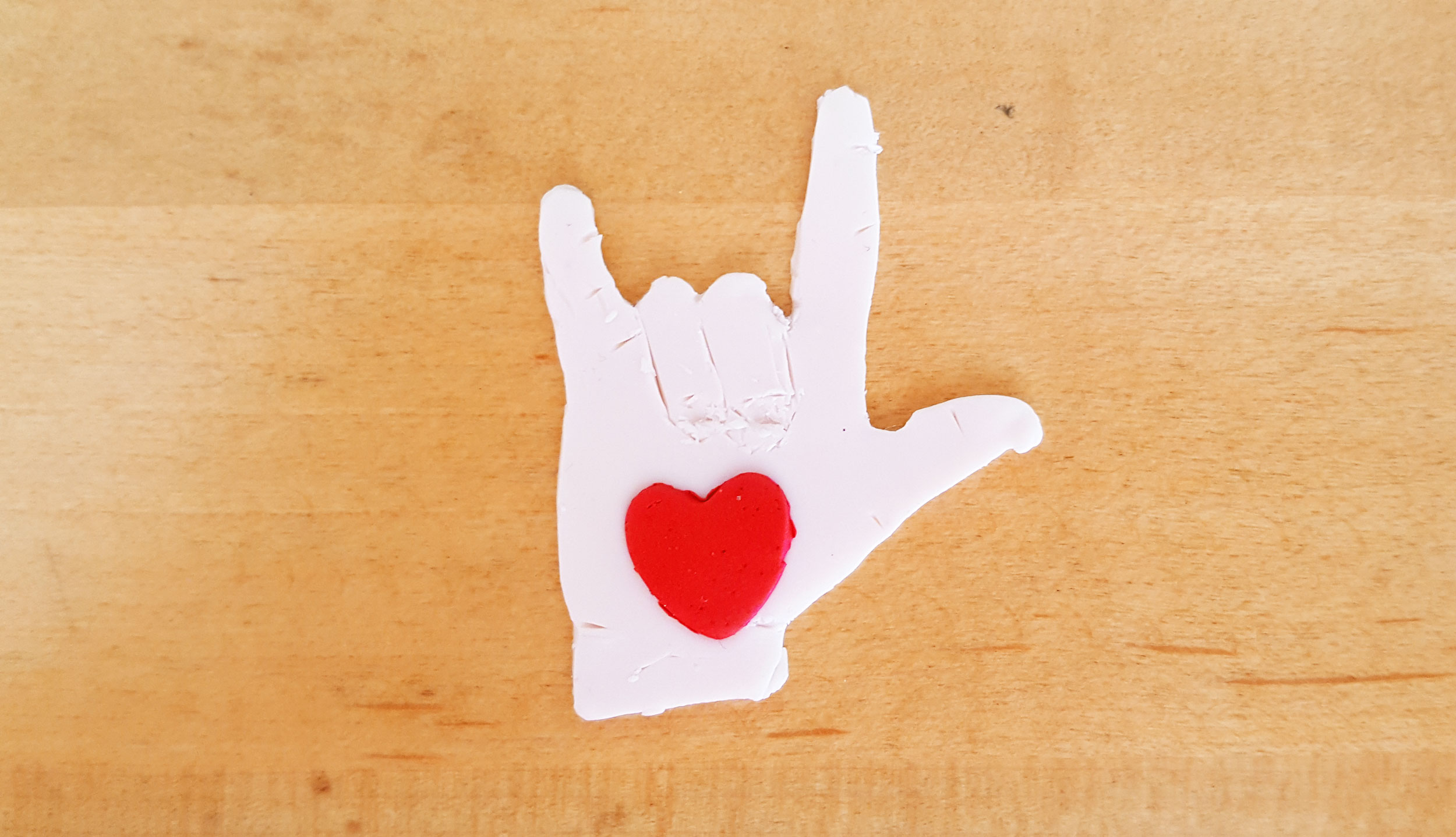 "Red heart on clay ""rock out"" hand