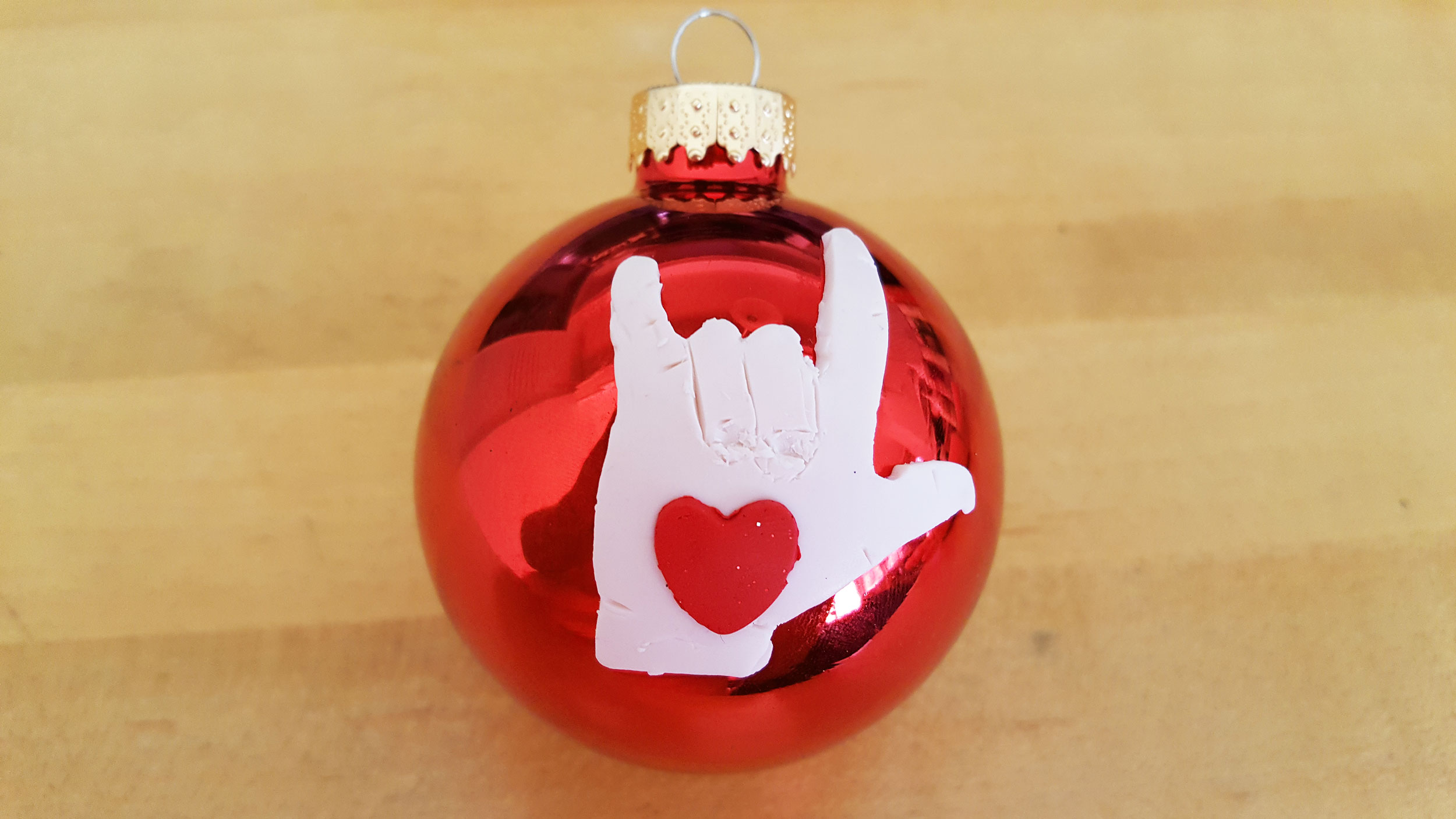 """Rock out"" hand with red heart on red glass ball ornament 