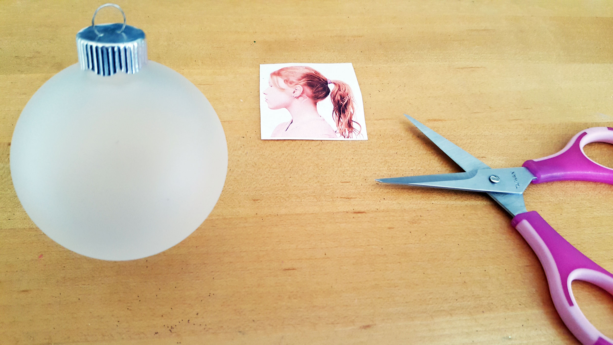 A frosted glass ball ornament next to a small pair of sewing scissors and a 2 inch tall cut out picture of a girl. | OrnamentShop.com