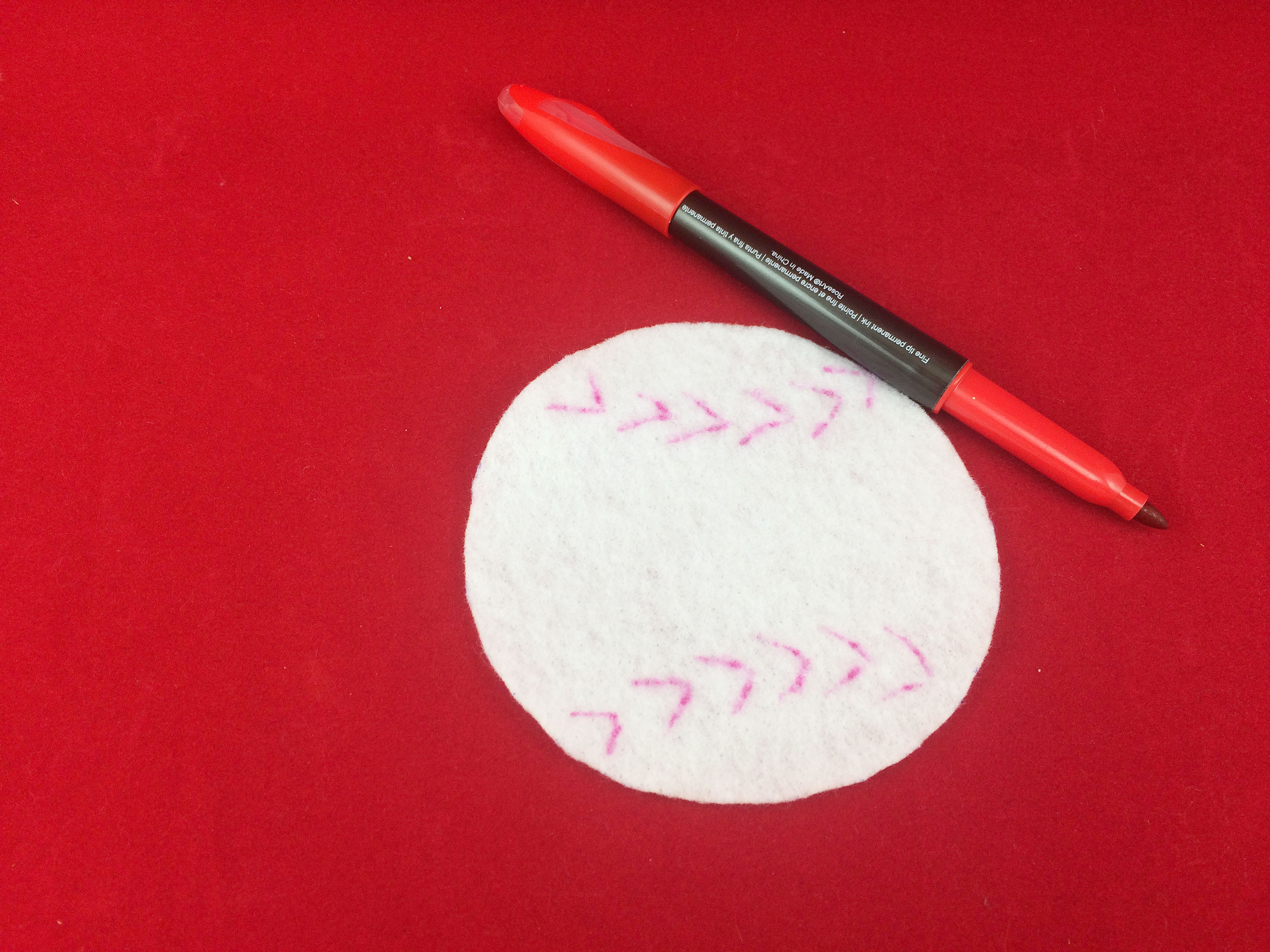 Cut out white felt circle. Red baseball stripes drawn with red marker. | OrnamentShop.com