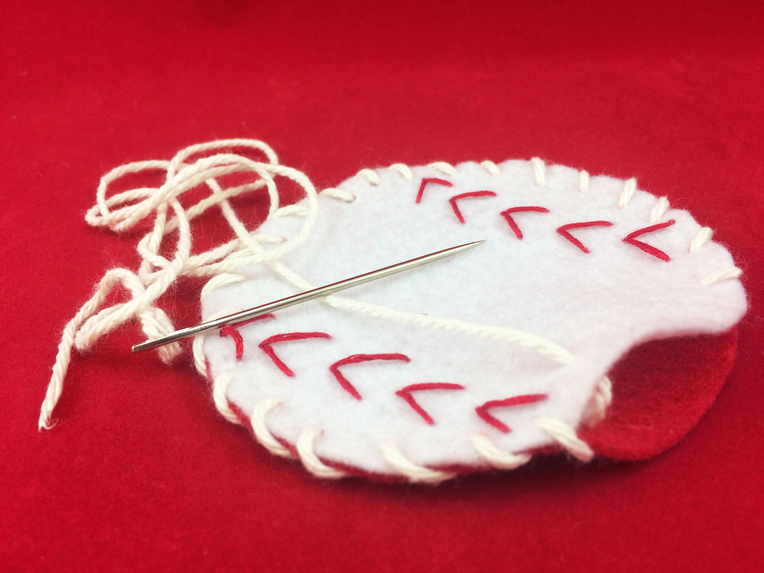 Red felt circle sewn to the back of white baseball with white string. | OrnamentShop.com