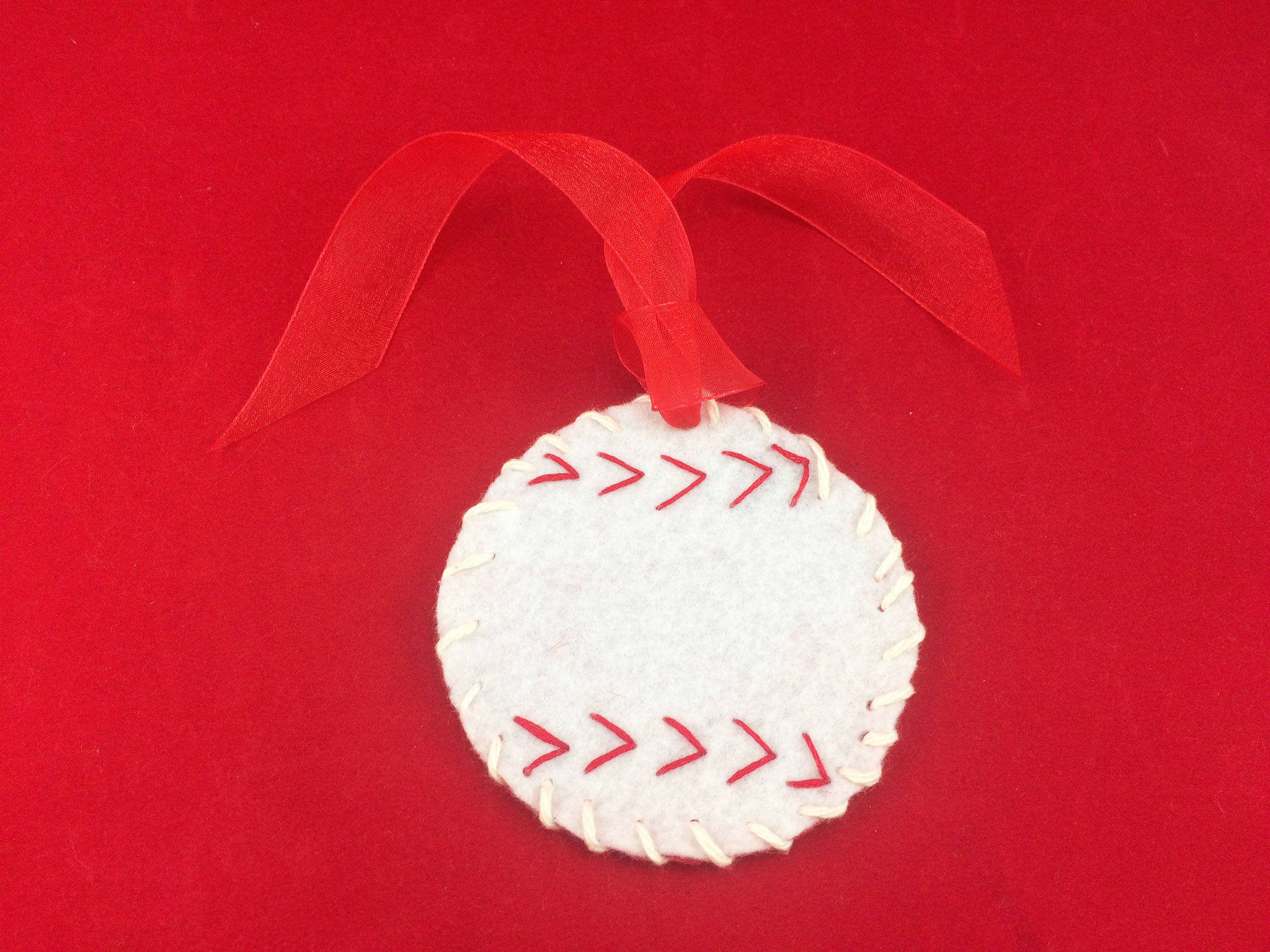 Ornament loop ribbon sewn to the top of the baseball using a needle. | OrnamentShop.com