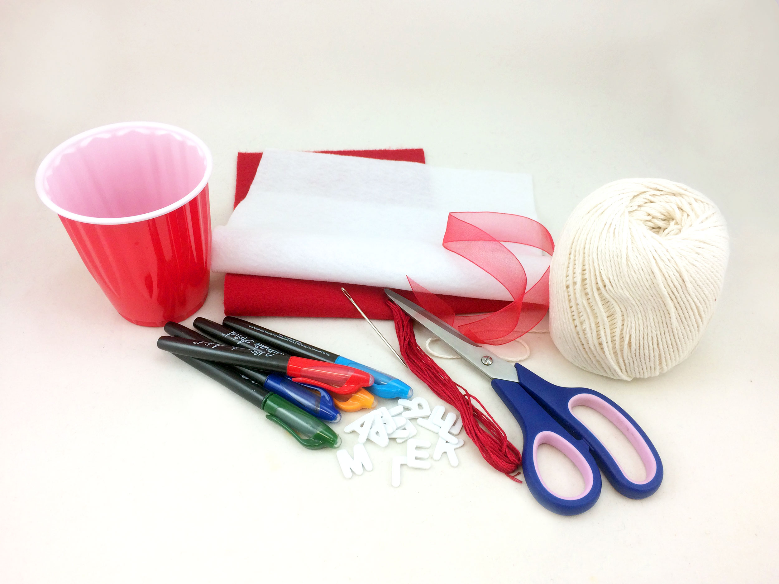 Baseball Ornament supplies on table, such as scissors, felt, markers, plastic cup, and string. | OrnamentShop.com