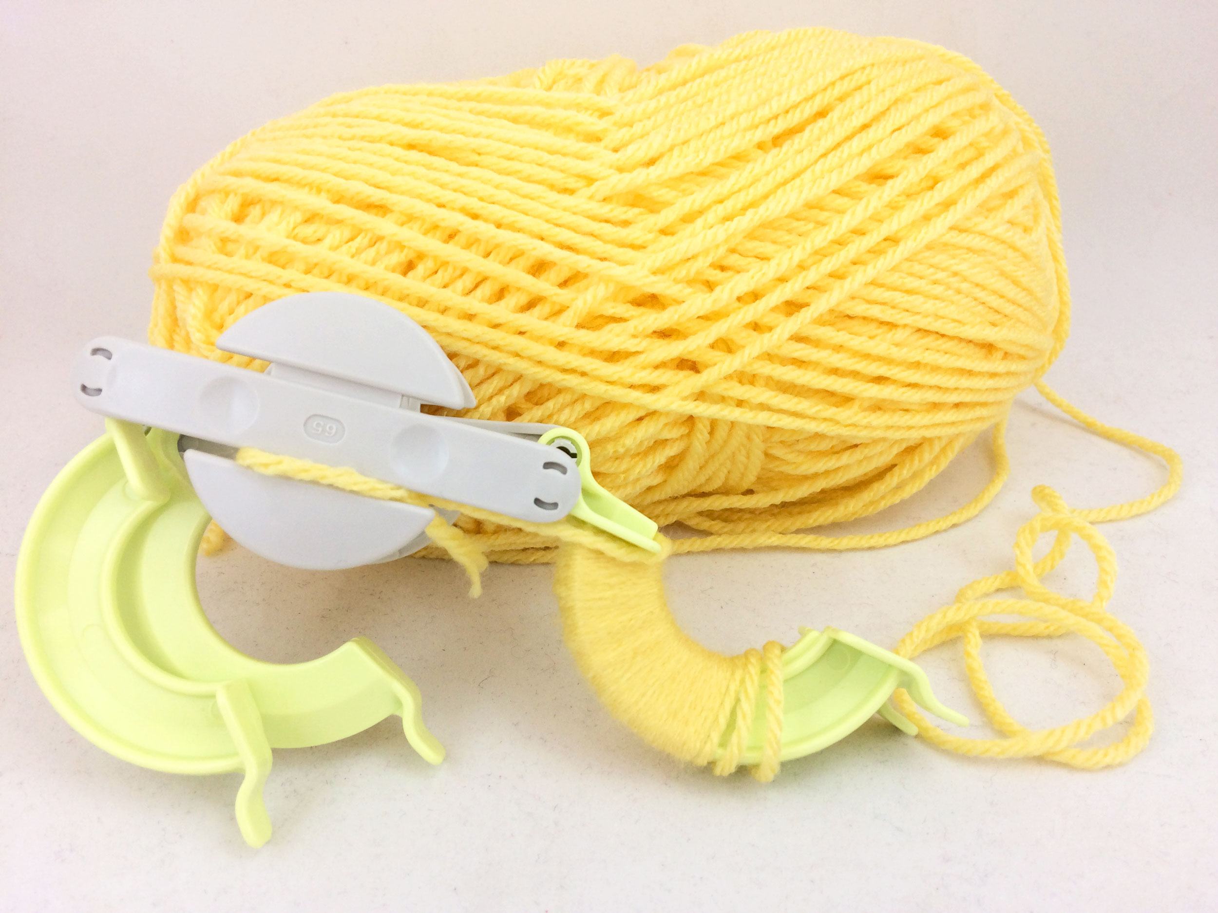 Wrap yarn around pom pom maker wings. | OrnamentShop.com