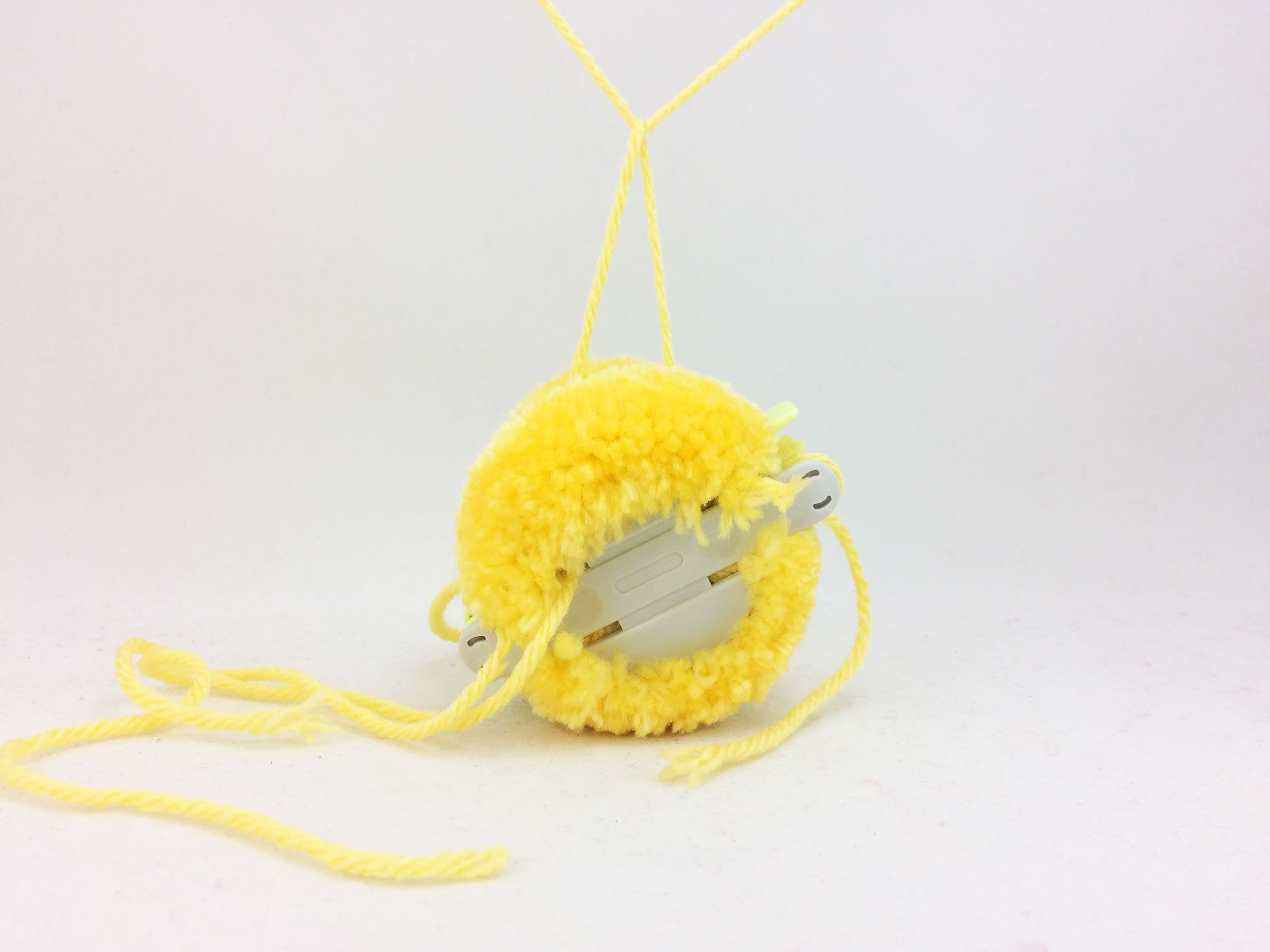 Tie yarn through center of pom pom maker to secure. | OrnamentShop.com