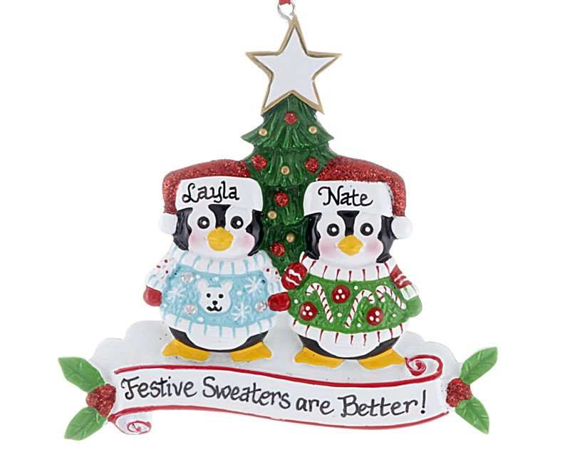 Two penguins stand in front of a Christmas tree personalized with names wearing sweaters. | OrnamentShop.com